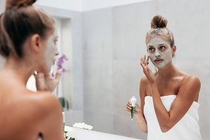 Beautiful woman applying mask