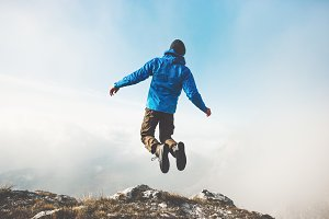 Happy Man jumping on mountains cliff