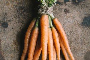 Bunch of fresh garden carrots on rusty background