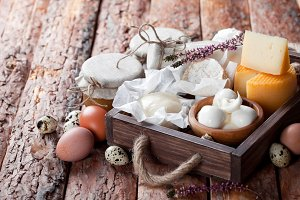 Fresh dairy products: cheese, butter, milk and eggs in wooden box