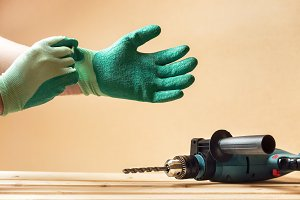 Man puts on protective gloves before drilling
