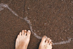 Top view of women legs toes on wet sand