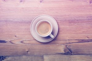Cup of coffee on wooden vintage board background