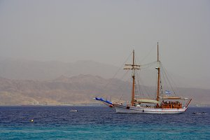 Walking on a wooden boat in the Red sea, Israel, with their sails, and mountains in the background