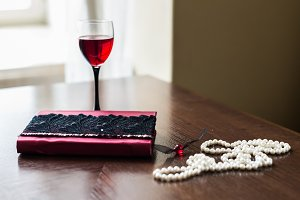 Book, glass of wine, beads