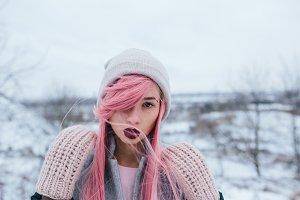 girl with pink hair posing at the camera