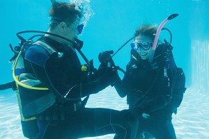 Man proposing marriage to his shocked girlfriend underwater in scuba gear