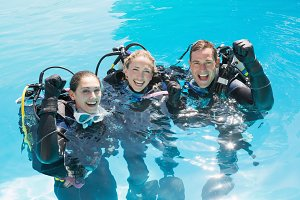 Smiling friends on scuba training in swimming pool cheering at camera