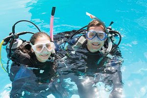 Smiling couple on scuba training in swimming pool looking at camera
