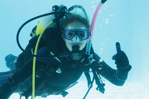Woman on scuba training submerged in swimming pool showing thumbs up