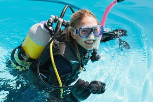 Smiling woman on scuba training in swimming pool