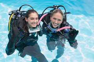 Smiling friends on scuba training in swimming pool making ok sign