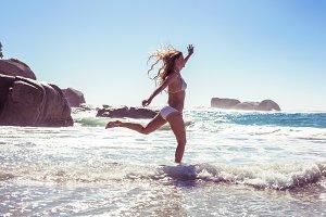 Beautiful smiling woman in white bikini skipping on the beach
