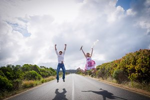 Excited couple jumping on the road