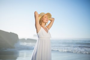 Smiling blonde standing at the beach in white sundress and sunhat