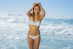 Gorgeous blonde in white bikini standing by the sea