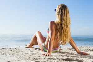 Gorgeous blonde in bikini and sunglasses on the beach posing