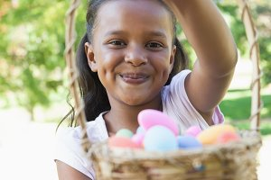 Little girl sitting on grass showing basket of easter eggs to camera