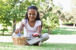 Little girl sitting on grass counting easter eggs smiling at camera