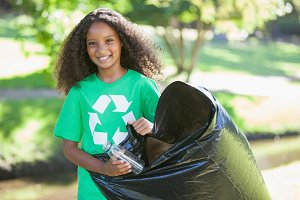 Young environmental activist smiling at the camera picking up trash