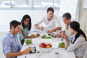 Workers chatting while enjoying healthy lunch