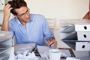 Casual businessmans workload getting bigger and bigger