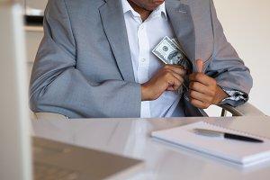 Dodgy businessman pocketing wad of dollars