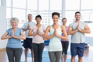 Sporty people with joined hands at fitness studio