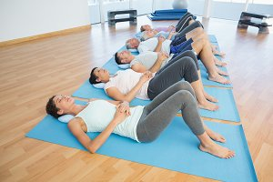 Class resting on mats in row at yoga class