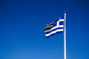 greek flag against a deep blue sky