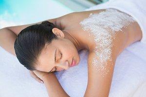 Calm brunette lying on towel with salt treatment on back
