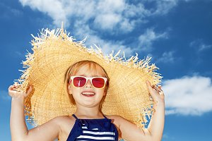 Happy girl in striped swimsuit and big straw hat on white beach
