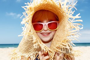 Happy girl in swimsuit playing with big straw hat on white beach
