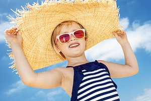 Happy girl in swimsuit and big straw hat against blue sky
