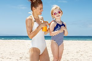 Happy mother applying sunscreen on girl in swimsuit at beach