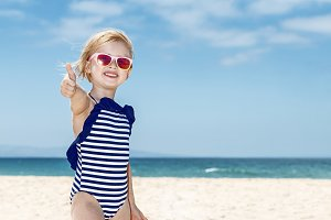 Happy girl in swimsuit on a white beach showing thumbs up