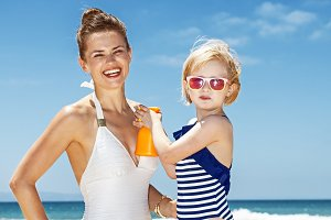 Child applying sunscreen on smiling mother in swimsuit at beach