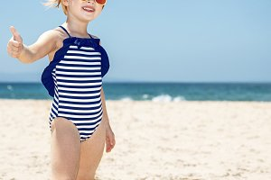 Happy girl in striped swimsuit on white beach showing thumbs up