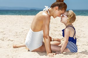 Smiling mother and child in swimsuits playing at sandy beach