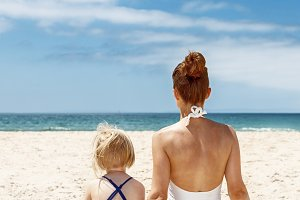 Seen from behind mother and child in swimsuits sitting at beach
