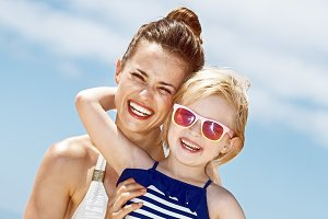 Happy mother and child in swimsuits hugging at sandy beach