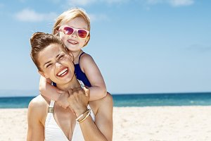 happy mother and child in swimsuits at sandy beach on sunny day