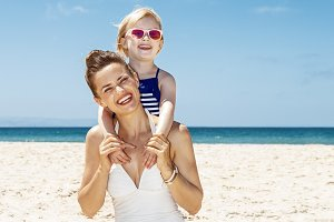Happy mother and girl in swimsuits at sandy beach on a sunny day