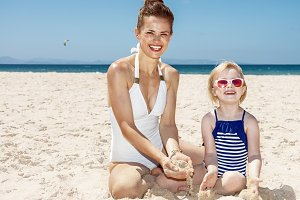 Happy mother and girl in swimsuits at beach playing with sand