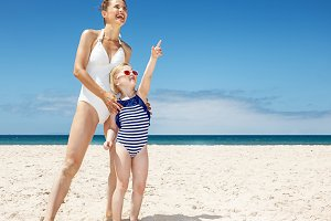 Happy mother and child pointing to somewhere at sandy beach