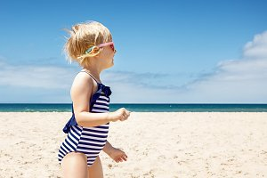 Happy girl in striped swimsuit on a white beach looking aside
