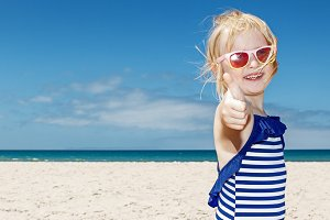 Girl in striped swimsuit on a white beach showing thumbs up