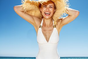 Smiling woman in white swimsuit and straw hat at sandy beach