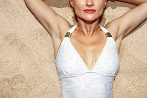 Closeup on relaxed woman in swimsuit laying on the sand
