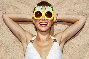 Smiling woman in swimsuit and pineapple glasses laying on sand